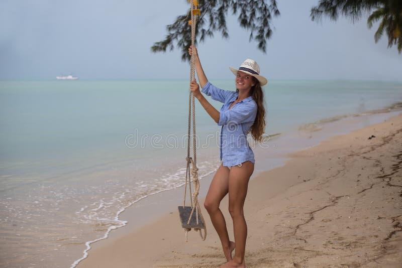 Sommersolarporträt der Mode einer Lebensart der jungen stilvollen Frau, sitzend auf einem Schwingen auf dem Strand, tragendes rei lizenzfreies stockfoto