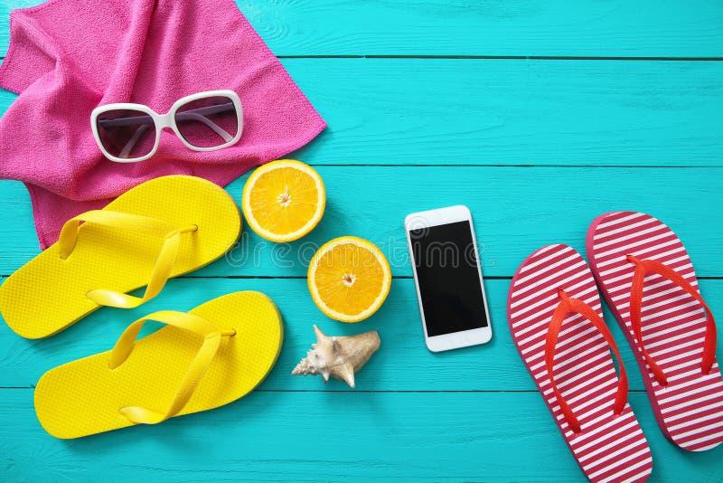 Sommerspaßzeit, Strandzubehör und Handy Blauer hölzerner Hintergrund Draufsicht- und Kopienraum lizenzfreie stockfotos