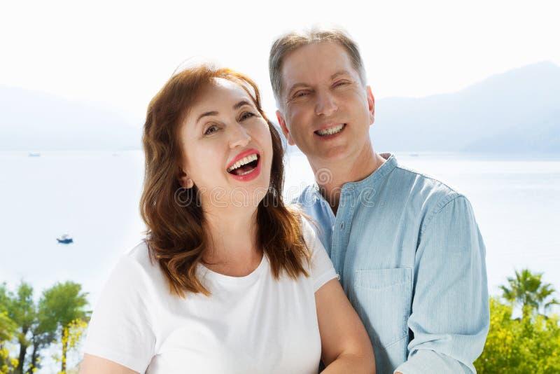 Sommerspa?wochenenden am tropischen Strand Gl?ckliche mittlere gealterte Familienpaare auf Naturseehintergrund Gesundes Verh?ltni stockbild