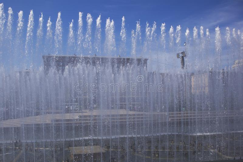 Sommerstadtbild mit Straße und Quadrat in der Abstandsabflussrinne die Wassermasse lizenzfreie stockfotos