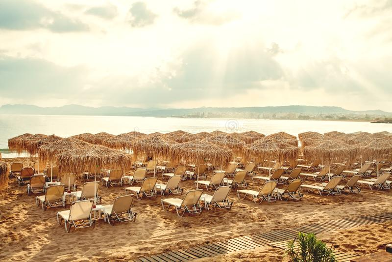 Sommerstrand mit Stroh Regenschirmen und sunbeds Ferien- und Feiertagskonzept lizenzfreie stockfotos