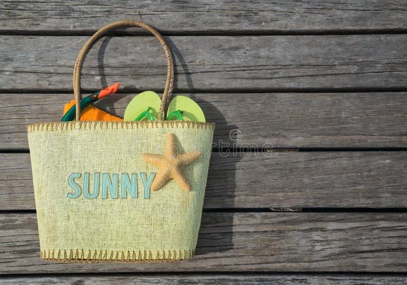 Sommerstrandtasche mit dem Text sonnig auf hölzernem Hintergrund stockbilder