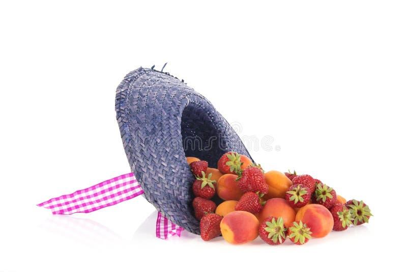 Sommerstrohhut mit abricots und Erdbeeren stockfoto