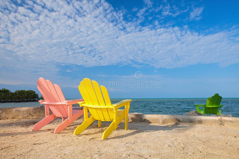 Sommerszene mit bunten Klubsesseln auf einem tropischen Strand stockfotografie