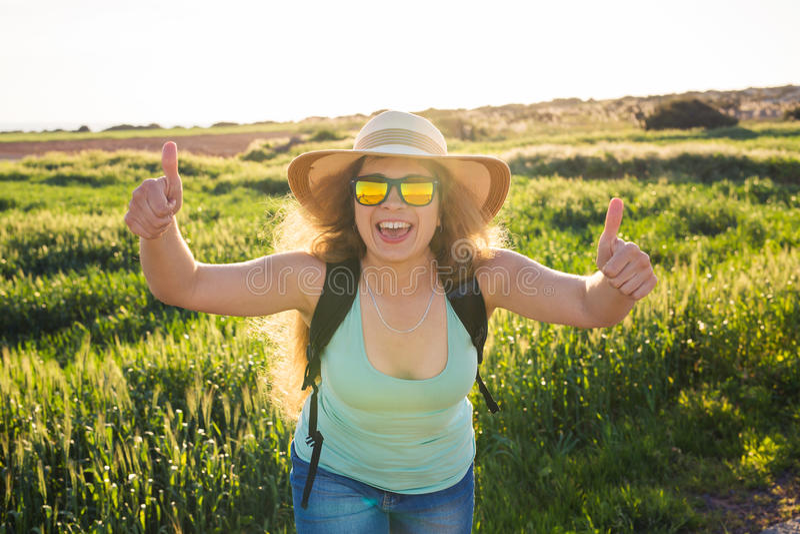 Sommerurlaubsreise und per Anhalter fahren Konzept - erfolgreiche glückliche Frau, die Daumen herauf anerkennend Geste auf Sommer stockfotografie