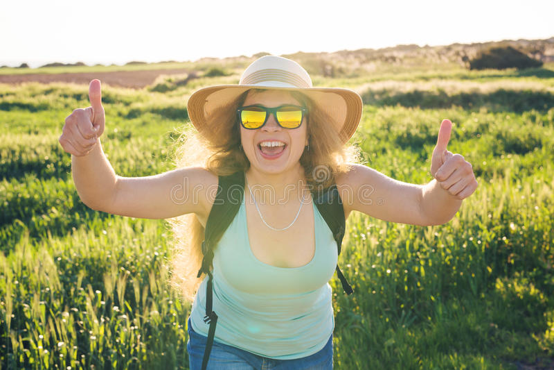 Sommerurlaubsreise und per Anhalter fahren Konzept - erfolgreiche glückliche Frau, die Daumen herauf anerkennend Geste auf Sommer lizenzfreie stockfotografie