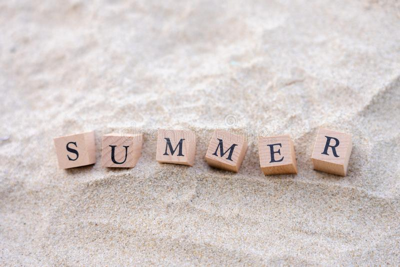 Sommerwort geschrieben auf den Holzklotz gesetzt auf den Sandstrand Seeansicht w?hrend der Tageszeit mit Hintergrund des blauen H lizenzfreie stockfotos