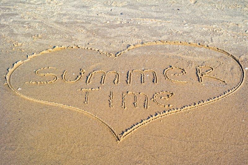 Sommerzeit geschrieben in den Sand lizenzfreie stockfotos
