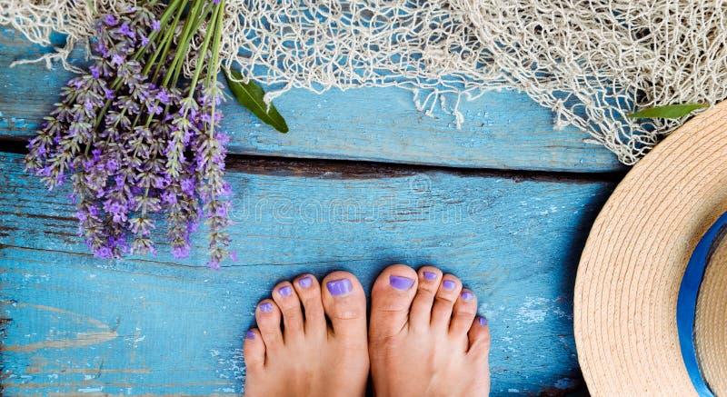 Sommerzeit-Seeferienhintergrund mit Strohhut, Weinlesefischernetz, Lavendelblumenstrauß und weiblichen Füßen auf verwittertem höl stockfoto