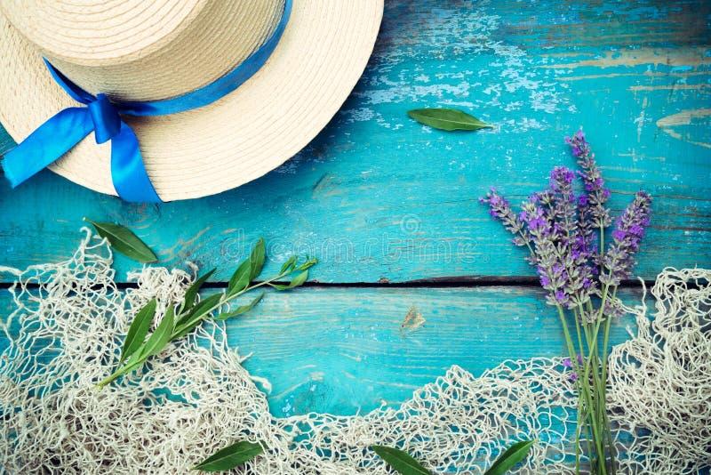 Sommerzeit-Seeferienhintergrund mit Strohhut, Weinlesefischernetz und Lavendelblumenstrauß auf verwittertem hölzernem blauem Hint lizenzfreie stockfotos