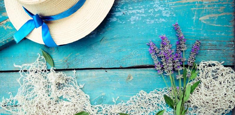 Sommerzeit-Seeferienhintergrund mit Strohhut, Weinlesefischernetz und Lavendelblumenstrauß auf verwittertem hölzernem blauem Hint lizenzfreies stockbild