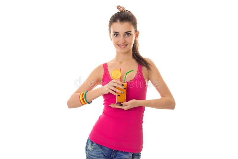 Sommerzeitporträt der jungen netten Brunettefrau mit dem Cocktail in ihrer Handaufstellung lokalisiert auf weißem Hintergrund lizenzfreie stockfotografie