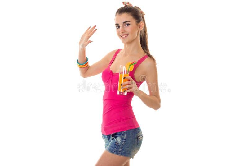 Sommerzeitporträt der jungen schönen Brunettefrau mit dem Cocktail in ihrer Handaufstellung lokalisiert auf weißem Hintergrund lizenzfreie stockfotos
