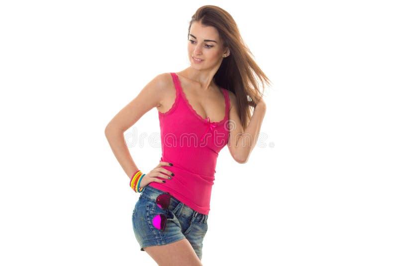 Sommerzeitporträt des jungen hübschen Mädchens in der hellen Kleidung mit der Sonnenbrilleaufstellung lokalisiert auf weißem Hint lizenzfreie stockfotografie