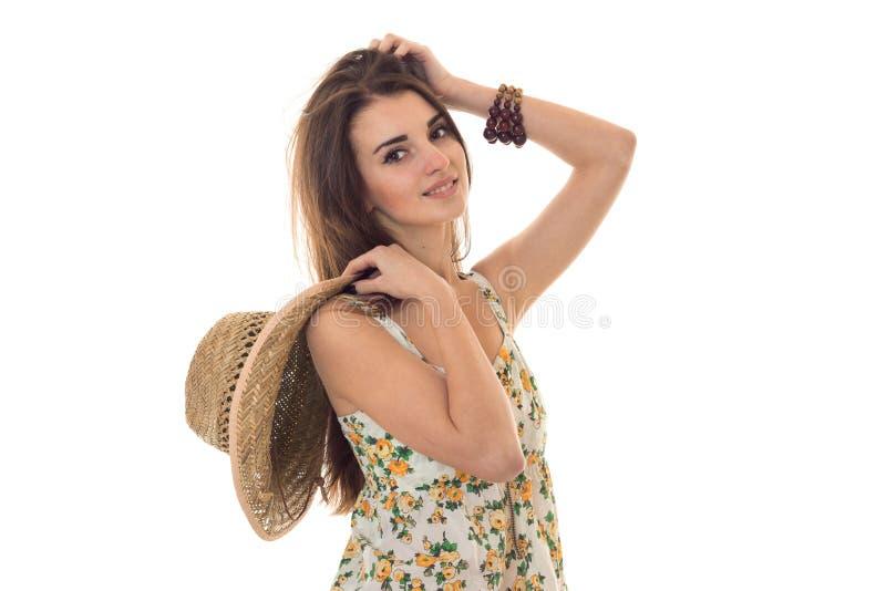 Sommerzeitporträt des jungen reizend Mädchens in der hellen Kleidung mit der Strohhutaufstellung lokalisiert auf weißem Hintergru stockfoto