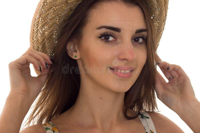 Sommerzeitporträt des jungen reizend Mädchens im Strohhut, der die Kamera und das Lächeln lokalisiert auf weißem Hintergrund betr stockbilder