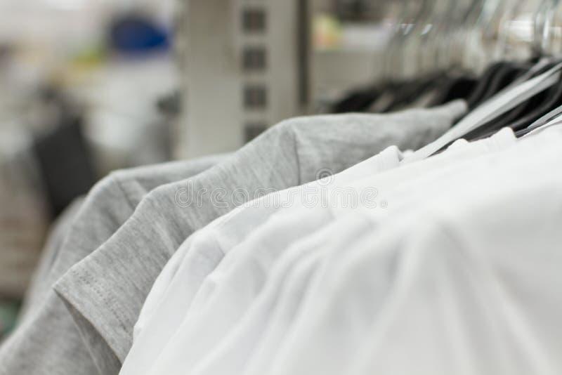 Sommige gebruikte kleren die op een rek in een vlooienmarkt hangen Achtergrond van kleding Selectieve nadruk stock fotografie