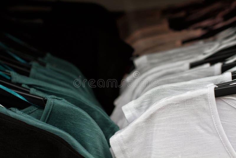 Sommige gebruikte kleren die op een rek in een vlooienmarkt hangen Achtergrond van kleding Selectieve nadruk stock foto