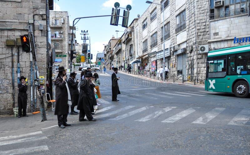 Sommige Joodse mensen wachten op het groene licht dichtbij de weg in Jeruzalem stock afbeeldingen