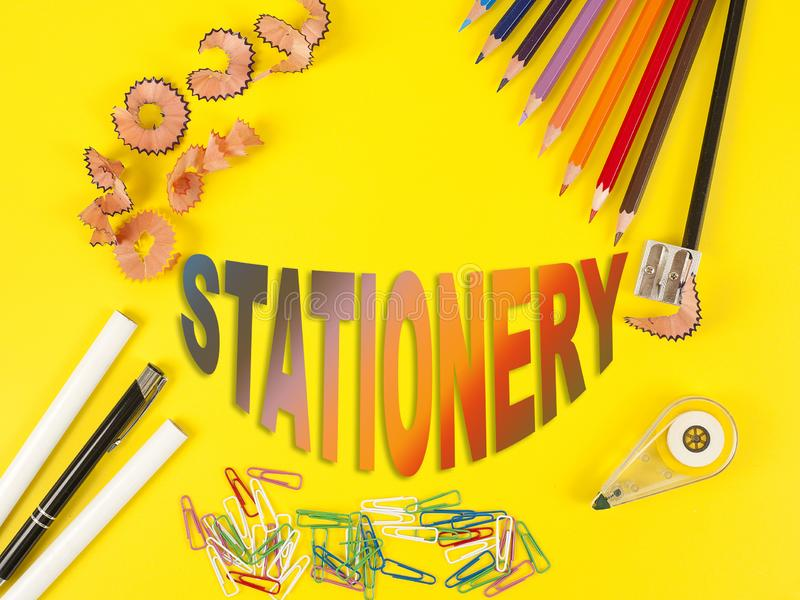 Sommige kleurpotloden van verschillende kleuren en een scherper en potloodspaanders op de gele achtergrond Word Kantoorbehoeften stock afbeeldingen