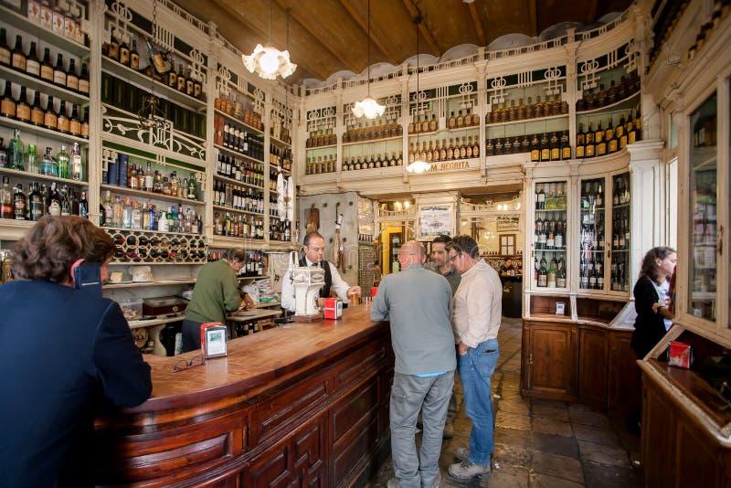Sommige mensen die wijn binnen oude stijlbar drinken met bezige barmannen en houten uitstekend decor stock afbeelding