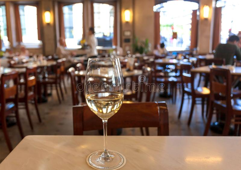 Sommige mensen die witte wijn binnen licht reusachtig restaurant in retro stijl drinken Vrije tijdsconcept stock afbeeldingen