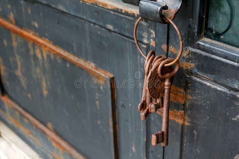 Sommige oude en roestige sleutels ketenen op een rustieke deur stock afbeelding