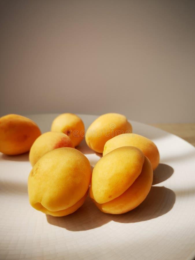 Sommige sappige rijpe zoete abrikozen liggen op een grote ronde witte plaat die zich op een houten lijst bevindt royalty-vrije stock afbeeldingen