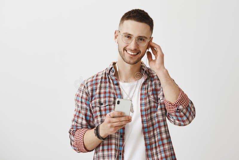 Sommige sporen betekenden om met oortelefoons worden geluisterd Portret van blij knap mannetje met charmante glimlach en in stock foto