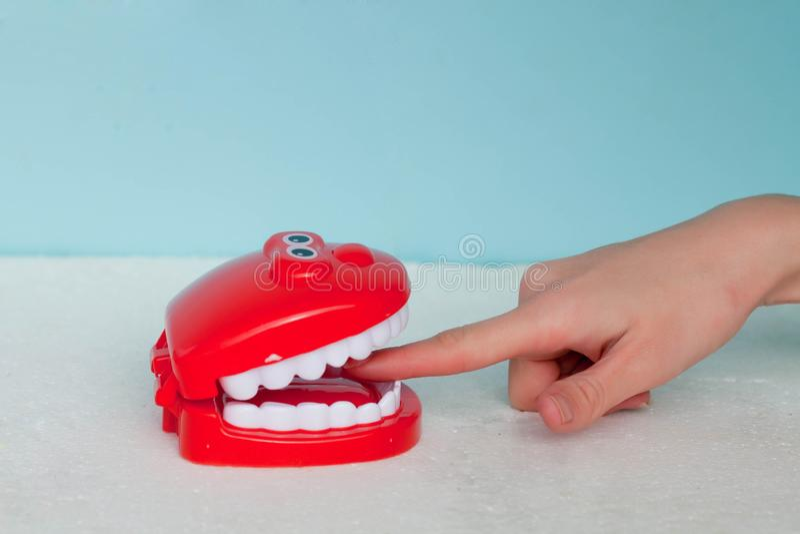 Sommige tanden die een vinger op een blauwe achtergrond bijten De vinger in een mond niet van bagage, en dat al hand zal worden a stock afbeeldingen