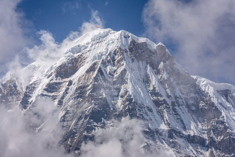 Sommità del sud di Annapurna circondata dalle nuvole aumentanti in Himalaya fotografia stock libera da diritti