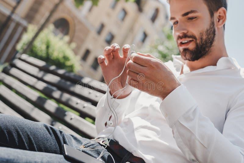 Soms is het productiefste ding u kunt doen ontspant De knappe mens houdt zijn oortelefoons terwijl het aanwezig zijn op een bank royalty-vrije stock afbeelding