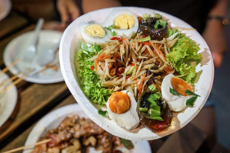 Somtum; Пряный салат папапайи с замаринованными рыбами в блюде бумаги на событии еды улицы foodtruck , Бангкок, Таиланд стоковое изображение