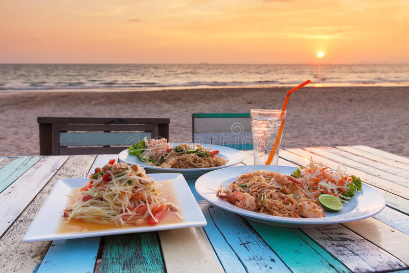 Somtum ,Pad Thai. Stir fry noodles with shrimp - and the view of sunset at Banana Garden Home on Klong Dao Beach - Lanta Island - Krabi - Thailand stock photos