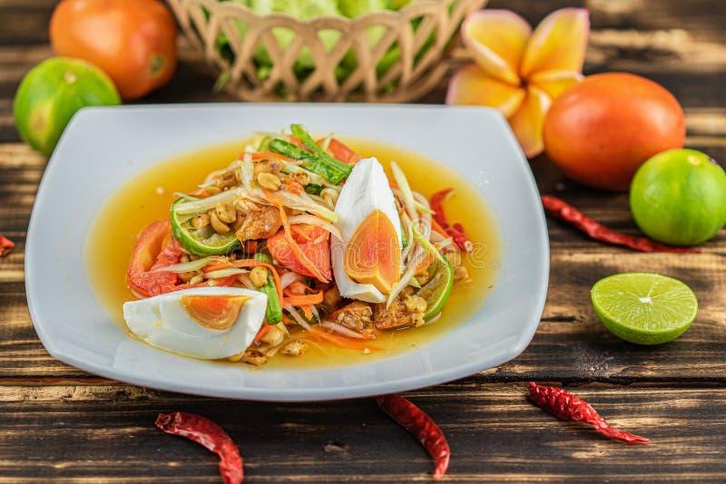 Somtum. Thai spicy green papaya salad with salted egg. Somtum. Thai spicy green papaya salad with salted egg on wooden table.Somtum khai kem stock images