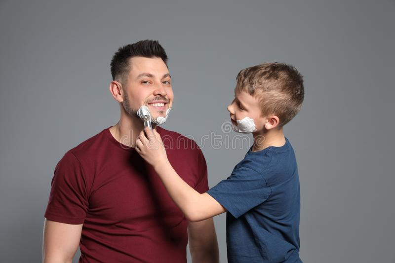 Son applying shaving foam on dad`s face, grey royalty free stock photography