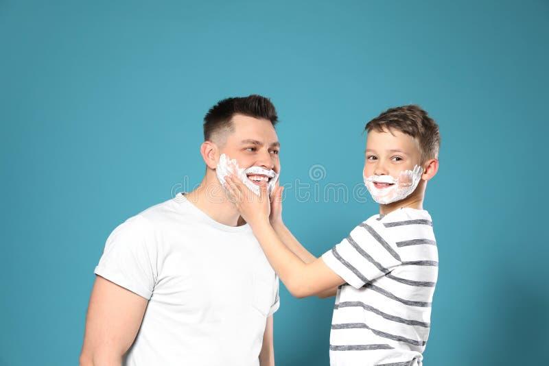 Son applying shaving foam on dad`s face royalty free stock image