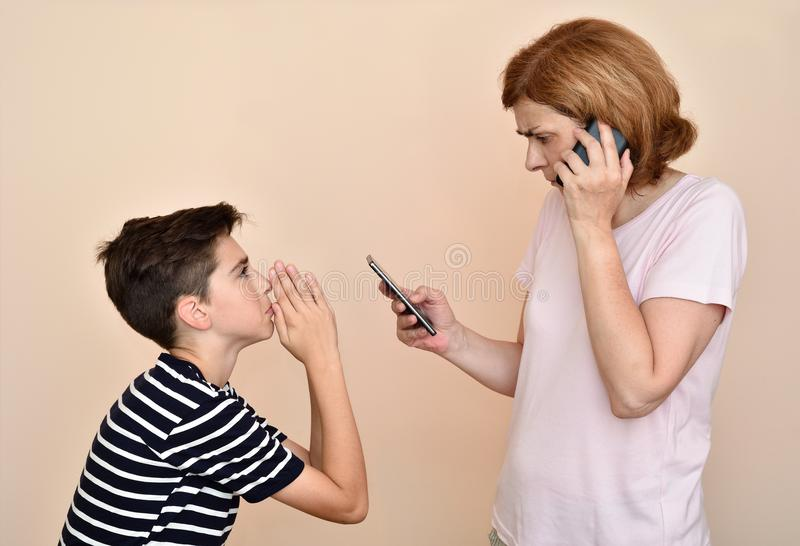 Son begging his angry and nervous mother for attention. She is using two smartphones at the same time and ignoring her son. Family and modern technology stock photos