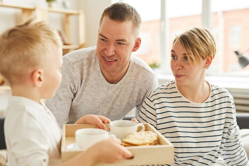 Son bringing breakfast to parents. Careful cute little son bringing breakfast to parents in bed while congratulating them on anniversary stock image