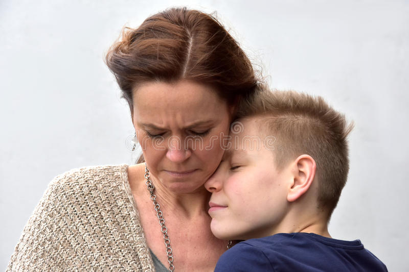 Son comforts mother stock image