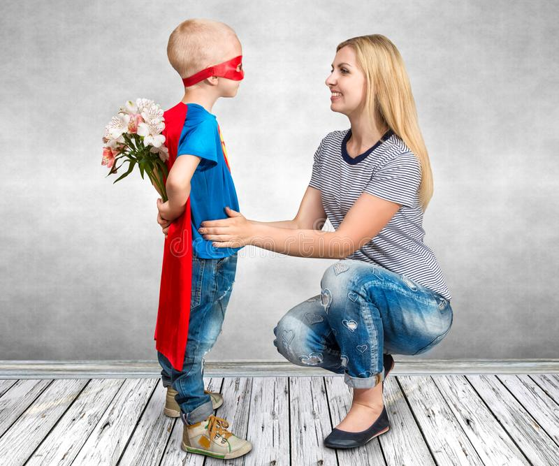 The Son In The Costume Of A Superhero Gives His Mother A Bouquet Of ...