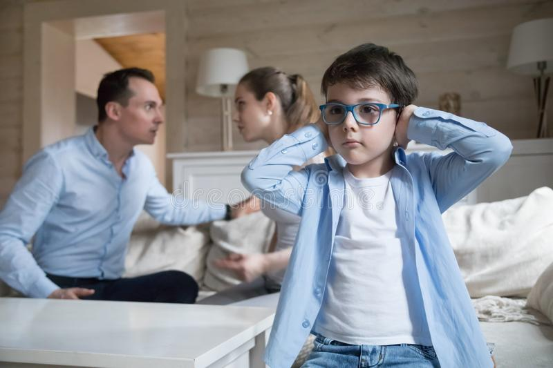 Son cover his ears with hands while parents quarreling stock photo