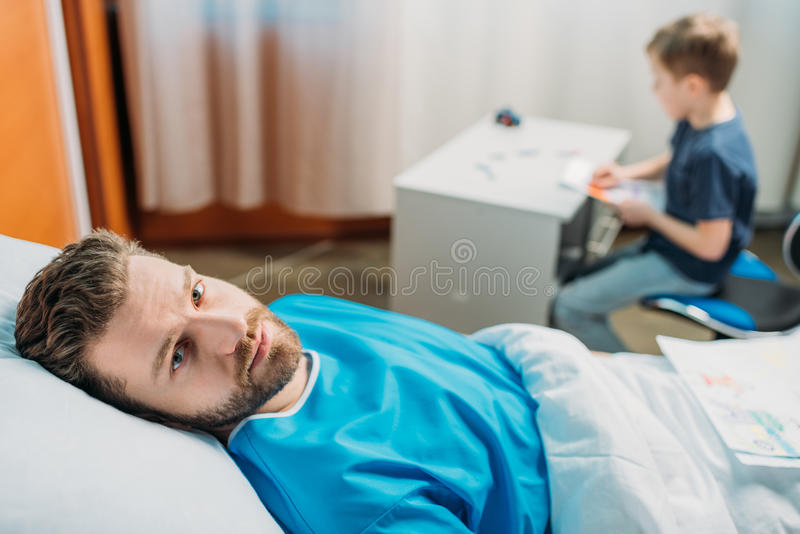 Son drawing pictures while sick father laying on hospital bed at ward. Dad and son royalty free stock images