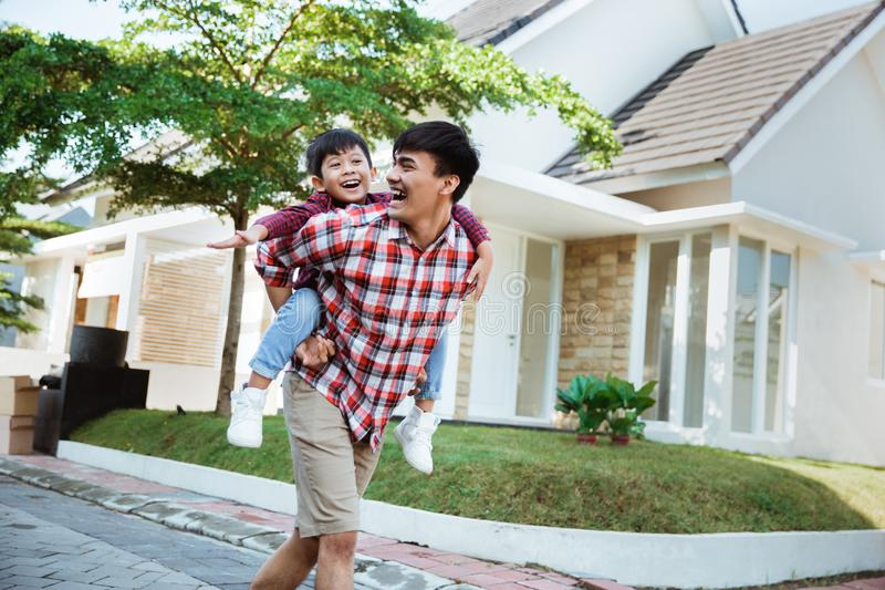 Son enjoy riding on his father`s back in the morning stock photos