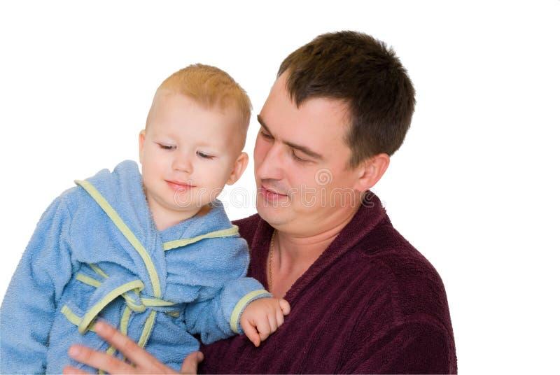 son för leende för håll för badrockdressingfader fotografering för bildbyråer