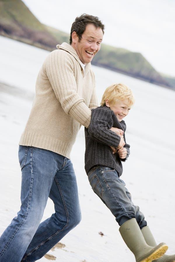 son för strandfaderholding fotografering för bildbyråer
