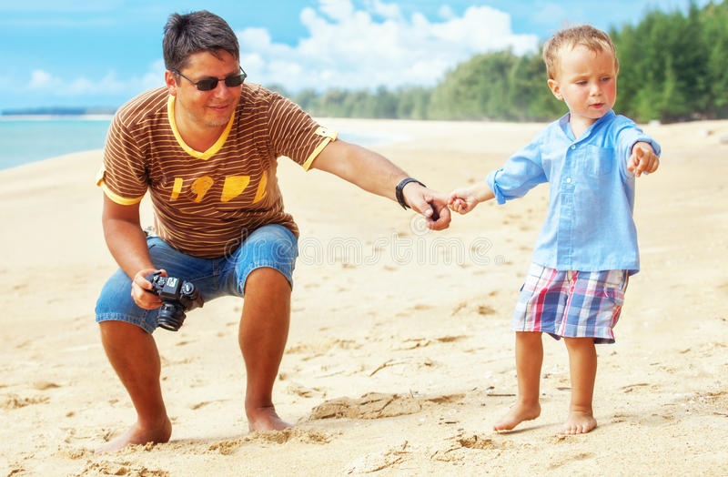 Son and father at the beach royalty free stock photography