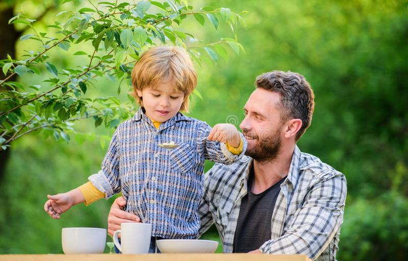 Son and father eating milk porridge. childhood happiness. healthy food and dieting. Family day. happy fathers day. Little boy with dad outdoor. Happy family stock images