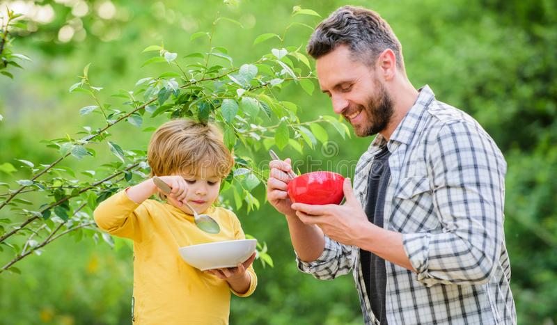 Son and father eating outdoor. healthy food and dieting. Dairy products. weekend morning breakfast. Happy family stock photography