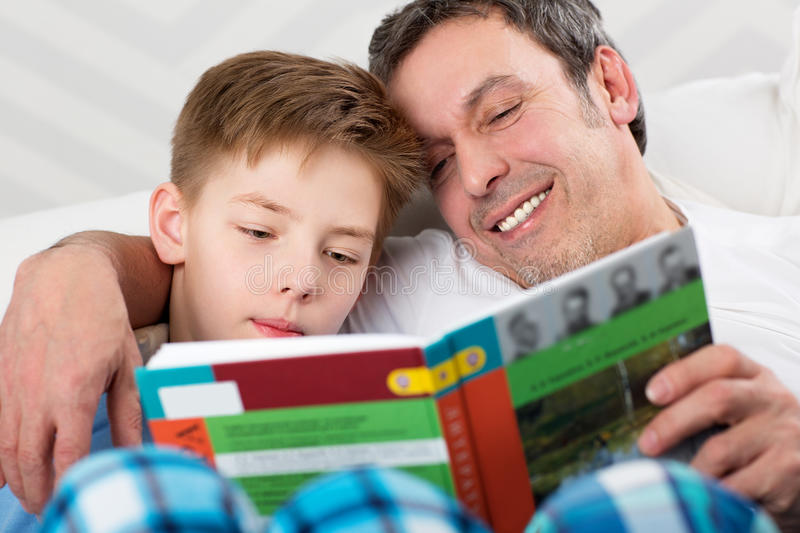 Son and father reading book together royalty free stock photography